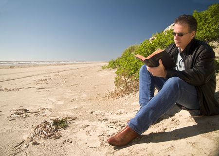 A man reading a holy bible sitting at the edge of a sand dune.  Archivio Fotografico