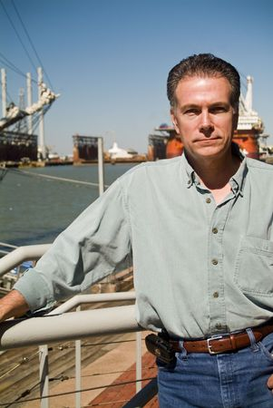 A man standing on a pier or deck with drilling rigs in the background.