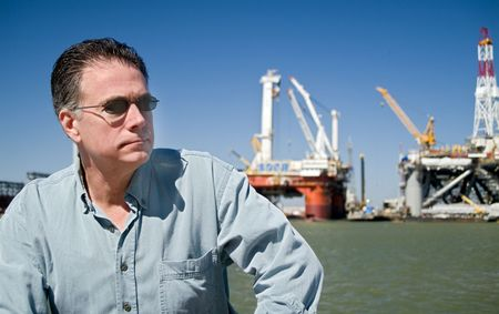 A man with drilling rigs in the background.