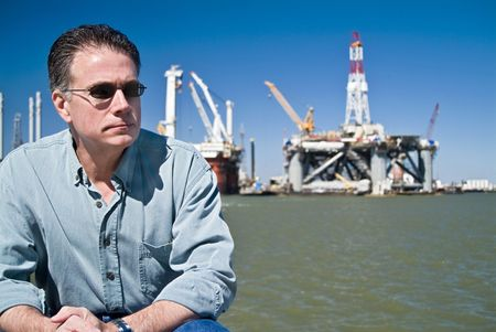 A man with drilling rigs behind him in the distance. Stock Photo