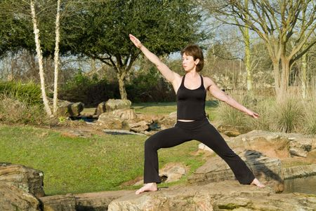 detoxification: A woman standing on a rock in a yoga posture called warrior pose.