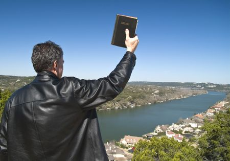 A man holding a bible in his raised hand, looking down over an affluent neighborhood.