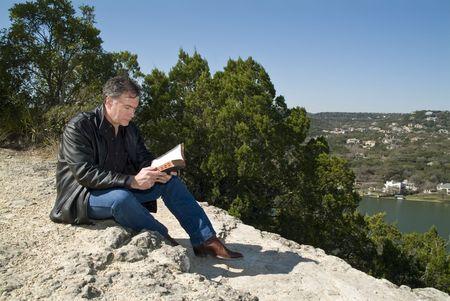 A man sitting on a rocky ledge reading a bible.