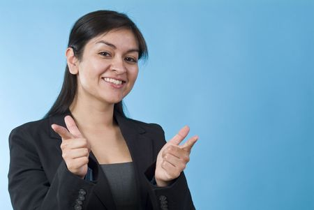 upwardly mobile: A pretty young woman smiling and making a affirming, pointing gesture at the camera.