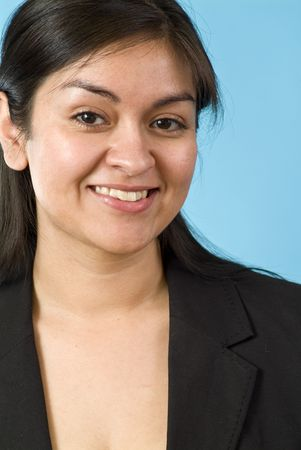 upwardly mobile: young Hispanic girl smiling for the camera in front of a blue screen Stock Photo