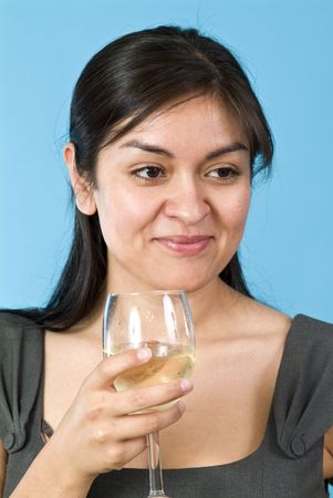A smiling, contented, pretty young woman holding a wine glass with liquid in it.  Banco de Imagens