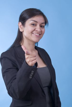 upwardly mobile: A pretty young professionally dressed woman making a pointing gesture to the camera.