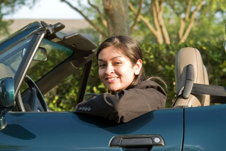upwardly mobile: A pretty young woman sitting in a convertible sports car smiling warmly.  Stock Photo