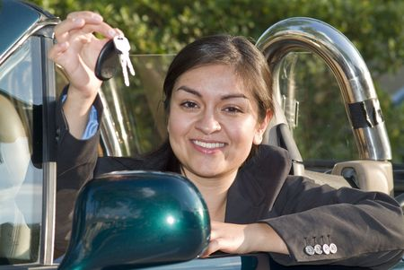 upwardly mobile: A pretty, smiling, young woman sitting in a sports car holding a set of keys in her hand.