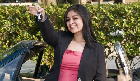 upwardly mobile: A pretty young woman holding out a set of car keys.  Stock Photo