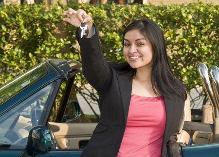 A pretty, smiling, young woman standing in front of a sports car holding out a set of car keys.  Standard-Bild