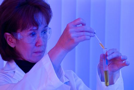 experimentation: A woman holding a dropper and a test tube with a red and blue lighting in the room.