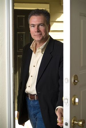 A man entering through his front door with a smile on his face.  Stock Photo