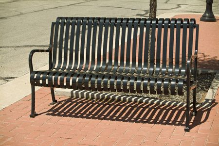 harsh: The harsh sun casting shadows from an empty, slotted, black, metal bench.