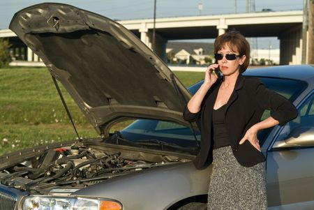 A woman with a cell phone and what appears to be car trouble.