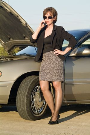 appears: A woman on a cell phone next to a car that appears to be out of service.  Stock Photo