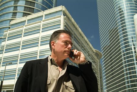 A man on a cell phone with large glass covered high rise office building in the back ground.  photo
