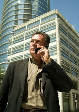 A man talking on a cell phone with large buildings in the back ground.  photo