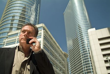 A man standing in front of some some towering office building talking on a cell phone.  photo