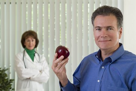 A man with an apple in his hand with a smiling woman dressed as a doctor, out of focus in the background. photo