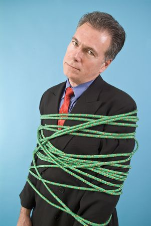 A business man restrained with a colorful rope with a discouraged look on his face.  Stock Photo