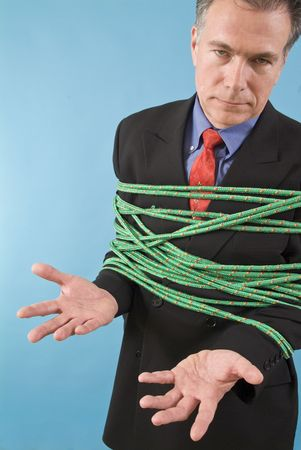 restraints: A man tied up with a colorful rope with a helpless posture and look on his face.