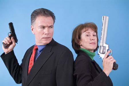 A man with a small automatic pistol in his hand looking confusedly at a woman with a very large revolver in her hand.  photo