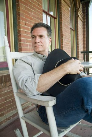 A man with a friendly smile, sitting on a porch in a rocking chair, holding a cowboy hat. photo