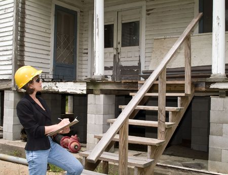 A woman in a hard hat, holding a clipboard, standing in front of an old house.