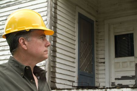 A man in a hard hat looking at an old rundown house.