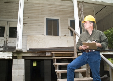 A man in a hard hat, holding a clipboard, standing on the steps of an old rundown house.