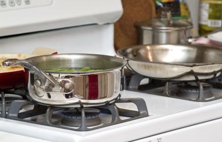 gas stove: A gas stove with two stainless steel pans on the burners. Stock Photo
