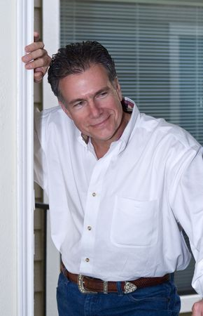 A man with a sheepish grin on his face looking inside a doorway