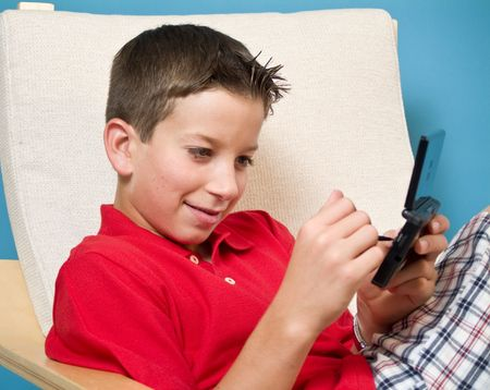 A boy sitting in a chair, playing with an electronic game board. Imagens - 3339695