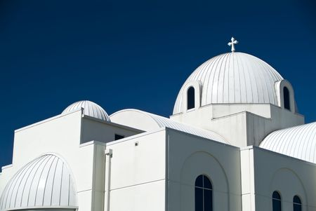 whose: A domed Christian church whose stark white color contrasts sharply wih the dark blue sky.