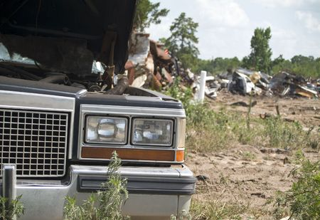 junked: An old wrecked vehicle with piles of scrap metal from an old car graveyard.