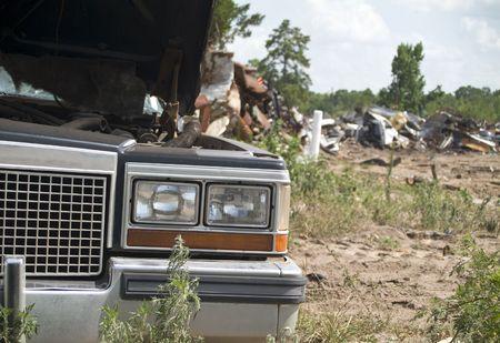 scrap metal: Un vecchio veicolo distrutto con i mucchi di rottami di metallo da un vecchio cimitero auto.