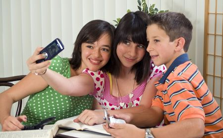 peers: Three kids taking a picture of themselves with a cell phone.
