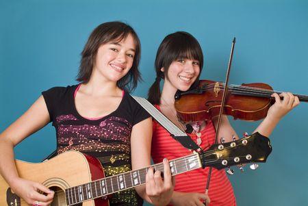two stroke: Dos ni�as sonriendo la celebraci�n de instrumentos de cuerda como si listos para entretener a usted.