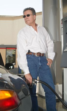 A man at a filling station, pumping gas into his vehicle.