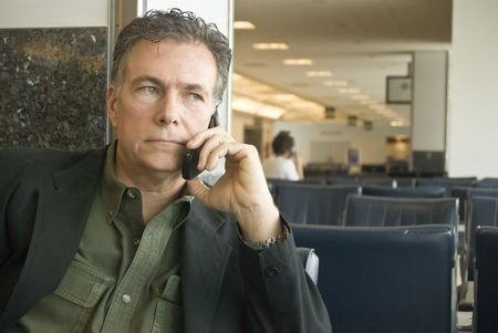 A man sitting in an airport talking on a cell phone.