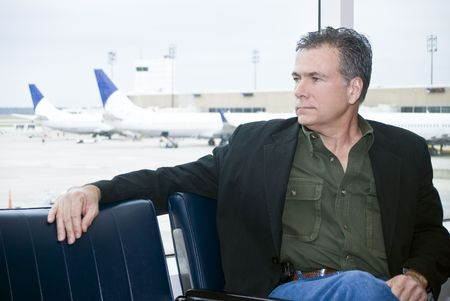 A man sitting by the windows of an airport with airplanes in the background.