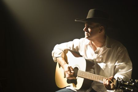A man in a cowboy hat, playing a guitar spotlighted through the darkness by a smoky beam of light