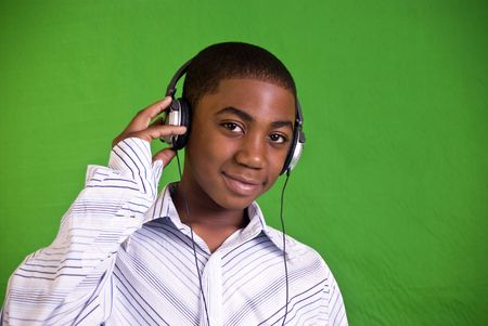 electronic music: An African American boy enjoying music he is hearing through his headphones.