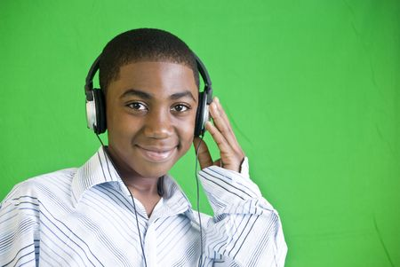 A young African American boy wearing headphones and smiling.