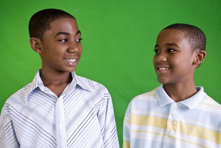Two young African American males smiling at each other as friends or brothers do.