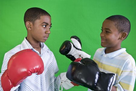 Two African American boys wearing boxing gloves as if ready to spar Archivio Fotografico