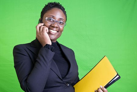 An African American businesswoman happily conducting business on her cell phone.