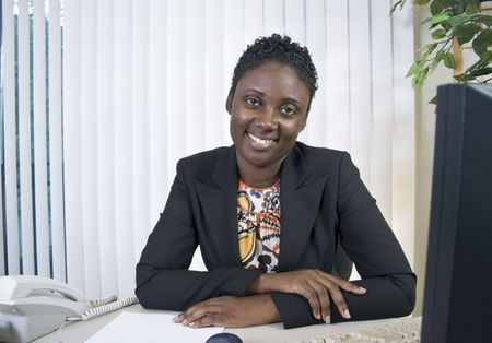 A lovely young Black woman in an office environment smiling a kind, friendly smile.  Archivio Fotografico