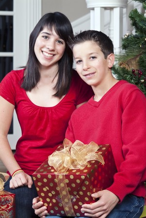 Two kids holding presents and smiling at the camera.
